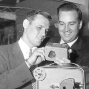 two men looking at movie camera