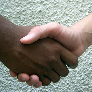 An African-American hand and a white hand shaking