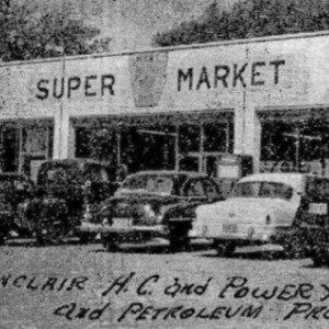 black and white image of super market with old fashioned cars parked out front
